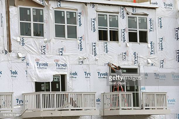 A construction worker helps to build a group of row houses under construction October 17 2012 in Chicago Illinois New home construction in the United...