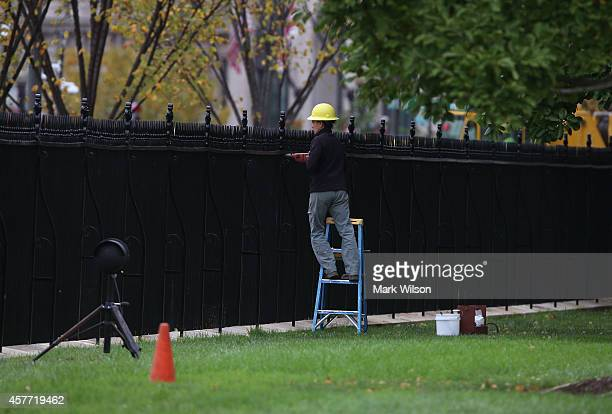 A construction worker helps with the restoration of the fence in front of White House October 23 2014 in Washington DC Last evening Dominic Adesanya...