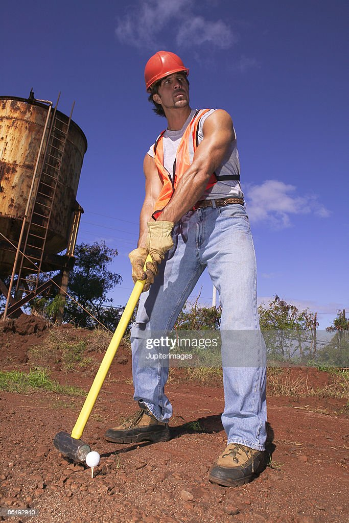 Construction worker hitting golf ball with sledgehammer : Stock Photo