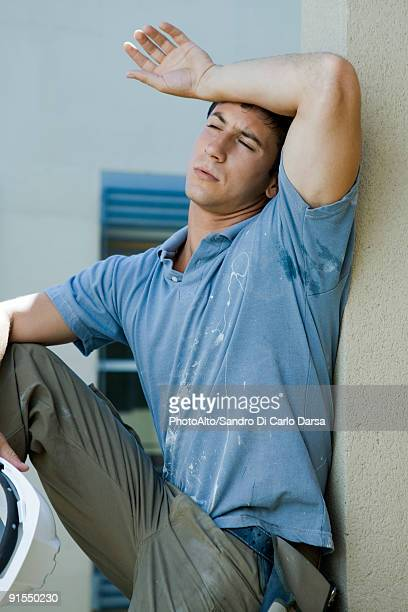 construction worker holding back of arm to forehead, eyes closed, taking break - polo t shirt photos et images de collection