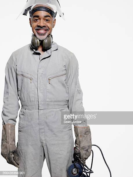 construction worker holding equipment, portrait, close-up - black jumpsuit stock pictures, royalty-free photos & images