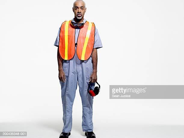 Construction worker holding headphones, portrait