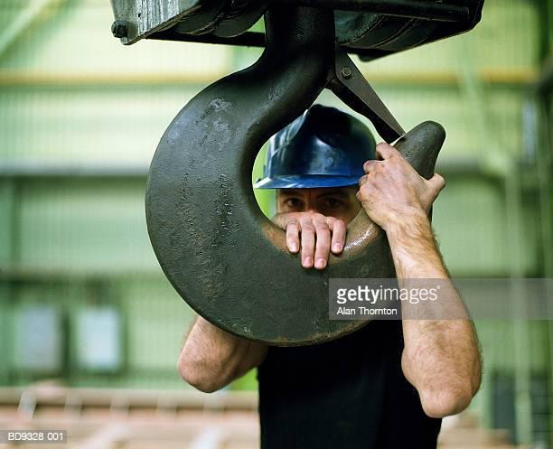 Construction worker holding onto industrial hook, portrait