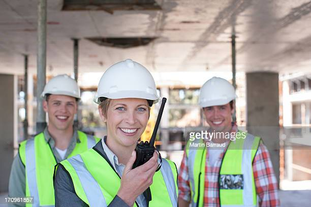 Construction worker holding walkie talkie on construction site