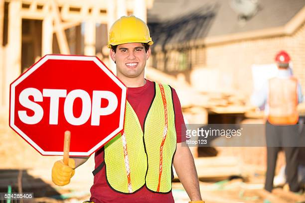Construction worker holds stop sign at building site. Traffic control.
