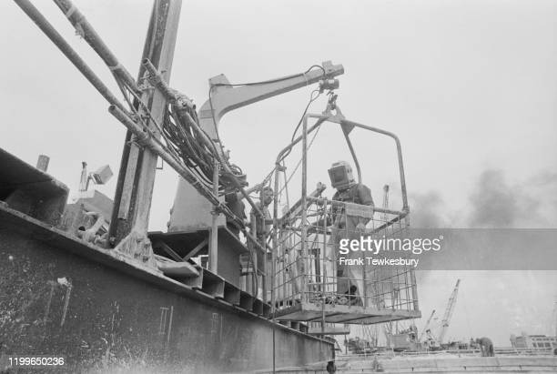 A construction worker in a cage is lowered by a hoist during construction of the Thames Flood Barrier on the River Thames London August 1976
