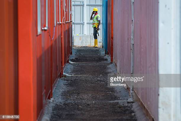 A construction worker in a hard hat and a hivisibility jacket stands near a construction site during a groundbreaking ceremony for Seletar Airport's...