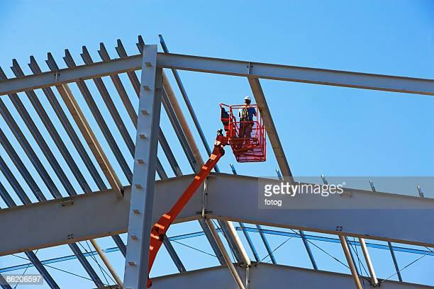 Construction worker in cherry picker