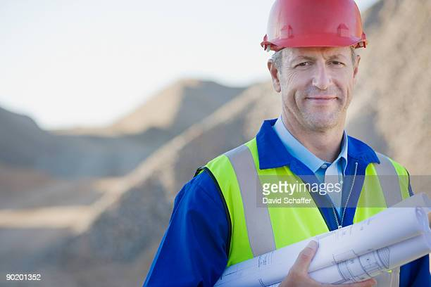 Construction worker in hard-hat holding blueprints