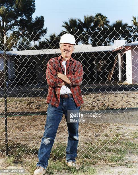 Construction worker in hardhat, standing by chain link fence, portrait
