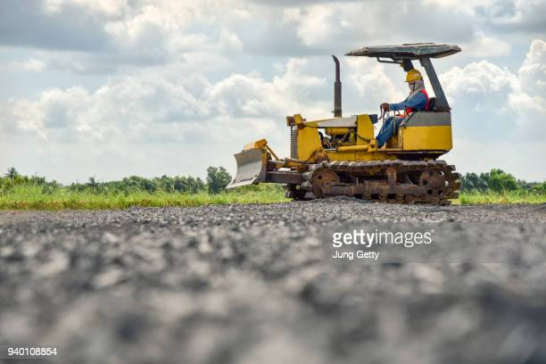 construction worker in safety uniform driving grader tractor or construction machine move the soil in construction site and beautiful sky background - 建設用機器 ストックフォトと画像