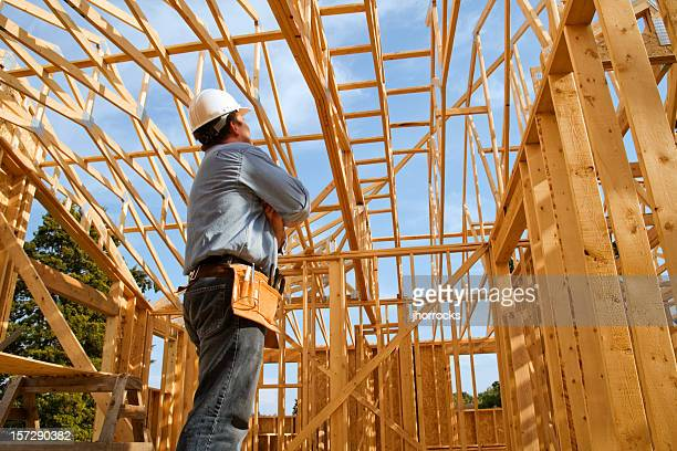 Construction worker in wooden building frame