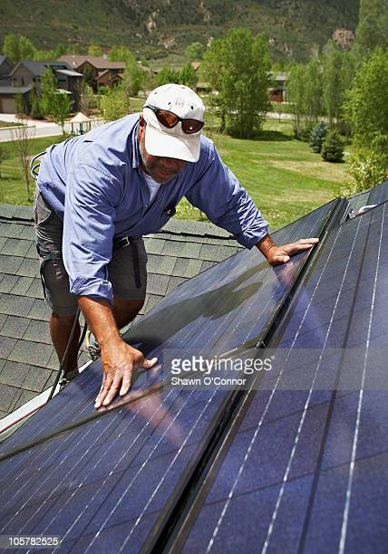 Construction worker installing solar panel on roof