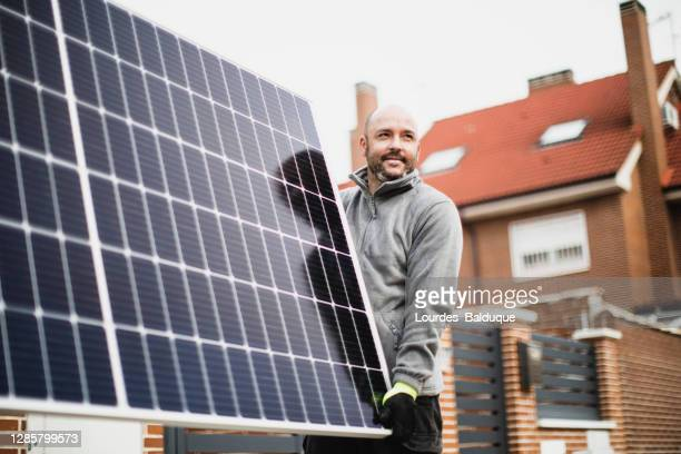 construction worker installing solar panels - solarkraftwerk stock-fotos und bilder