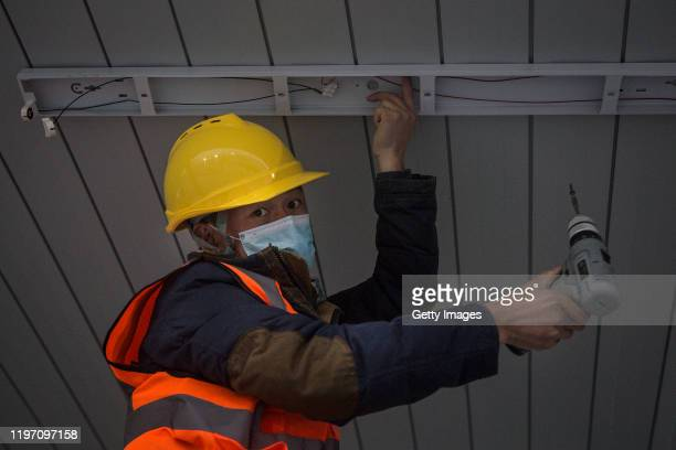 A construction worker installs lighting as new hospitals are built to tackle the coronavirus on January 28 2020 in Wuhan China Wuhan Huoshenshan...