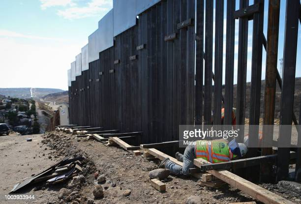 Construction workers install new fencing along the USMexico border fence on July 21 2018 in Tijuana Mexico The US House is proposing a bill which...