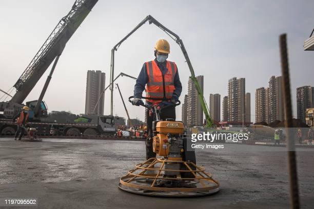 A construction worker is pictured amidst heavy machinery as new hospitals are built to tackle the coronavirus on January 28 2020 in Wuhan China Wuhan...