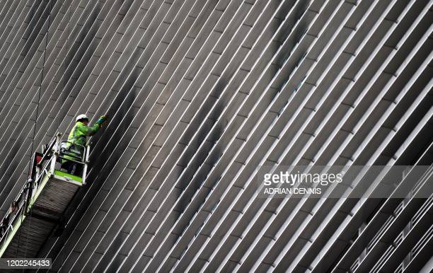 Construction worker is seen cleaning a new building at The Royal London hospital where British Prime Minister David Cameron and Swedish Prime...