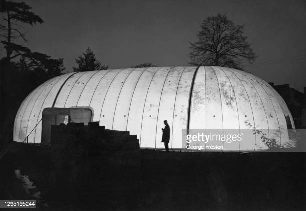 Construction worker is silhouetted as the 50,000 cubic foot nylon 'air house' is illuminated, enabling construction work to continue into the night,...