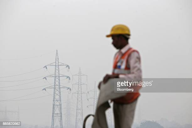 A construction worker labors as electricity pylons standing in the distance are shrouded in smog in New Delhi India on Monday Dec 4 2017 The World...