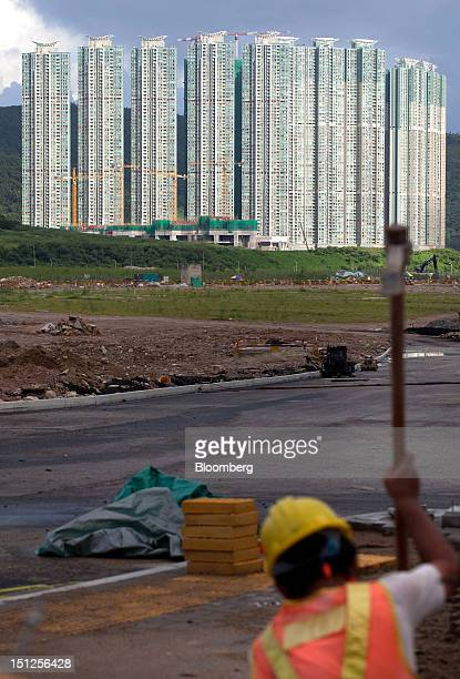 A construction worker labors in front of residential tower blocks in the Tseung Kwan O area of the New Territories in Hong Kong China on Tuesday Sept...