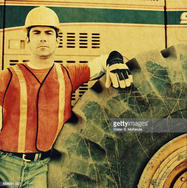 Construction worker leaning on bulldozer (paper negative)