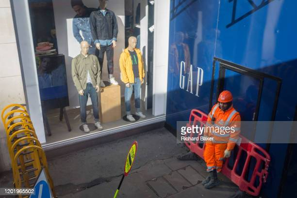 A construction worker leans against a barrier in front of the entrance to a project and alongside the window display of clothing retailer GAP in...