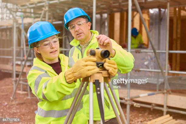 construction worker learning how to use a builder's level