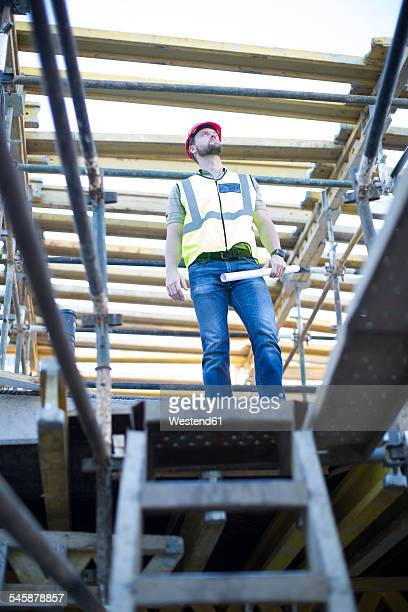 Construction worker looking at top of staircase