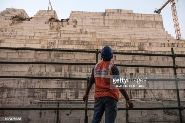Construction worker looks at the Grand Ethiopian Renaissance Dam , near Guba in Ethiopia, on December 26, 2019. - The Grand Ethiopian Renaissance...