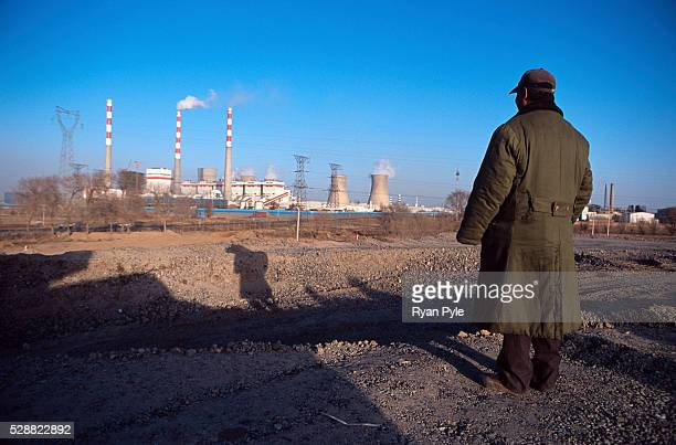 Construction worker looks out over a new rail line between Xi'an and Baotou, in Baotou, Inner Mongolia, China. A coal-fire plant rises in the...