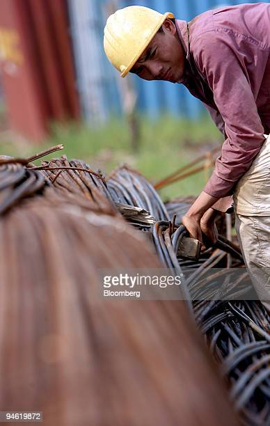 A construction worker looks over steel rods on a building site in Hanoi Vietnam on Sunday August 20 2006