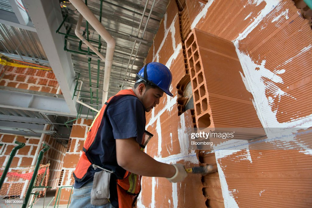A Construction Worker Make Adjustments To Brick Wall At Empresas ICA SABs Marina Apartment Complex