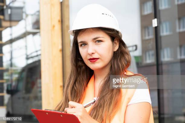 construction worker making notes on clipboard - sigrid gombert stock pictures, royalty-free photos & images