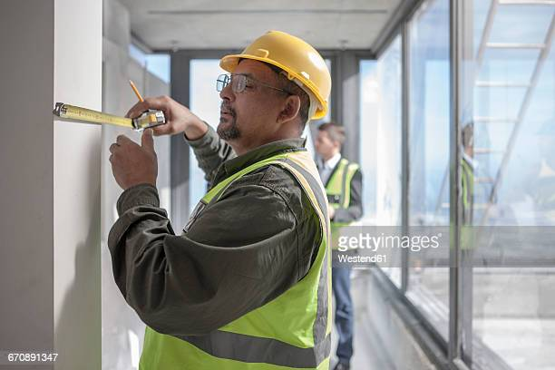 Construction worker measuring on construction site