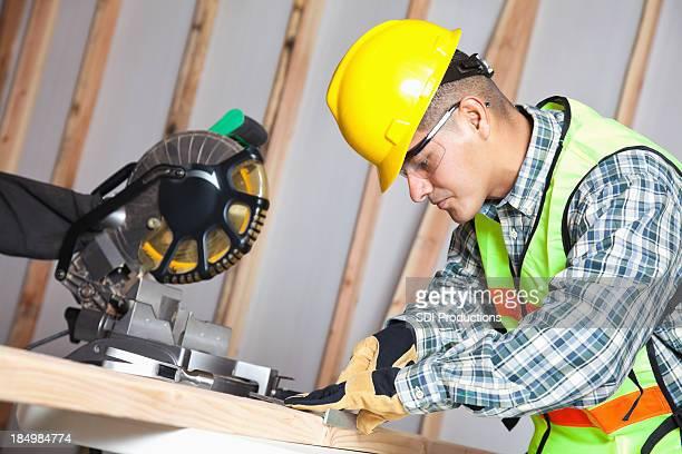 Bauarbeiter messen Holz mit V-Muster auf der Website gesehen