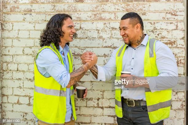 Construction Worker Men in High Vis Vests Having a Coffee Break