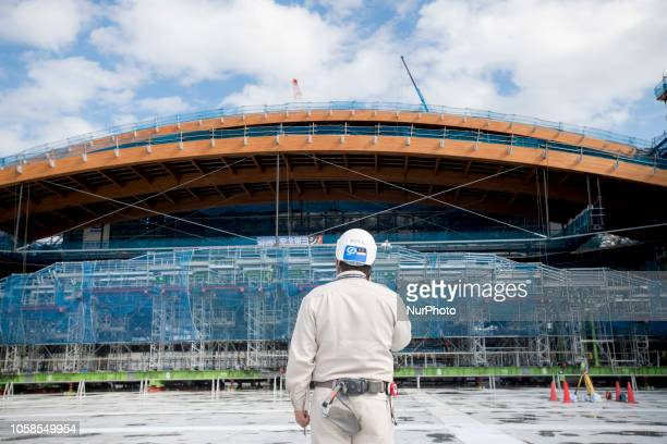 A construction worker monitors as the centre section of the timber roof is raised at the Ariake Gymnastics Centre construction site ahead of the...