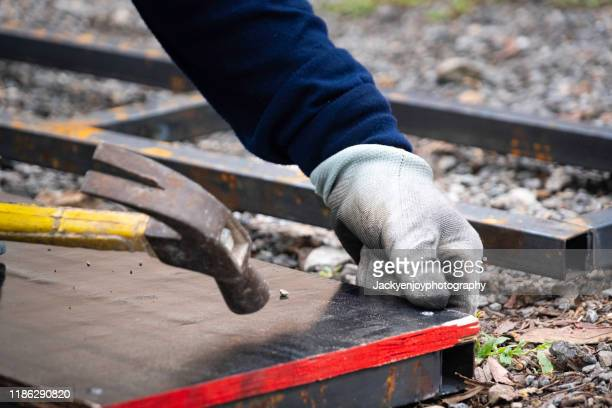 construction worker nailing wood board with hammer - foundation make up stock pictures, royalty-free photos & images