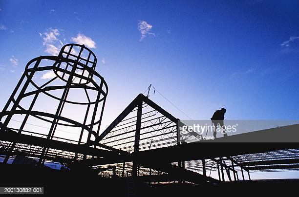 construction worker on beam, silhouette, low angle view - image stock pictures, royalty-free photos & images