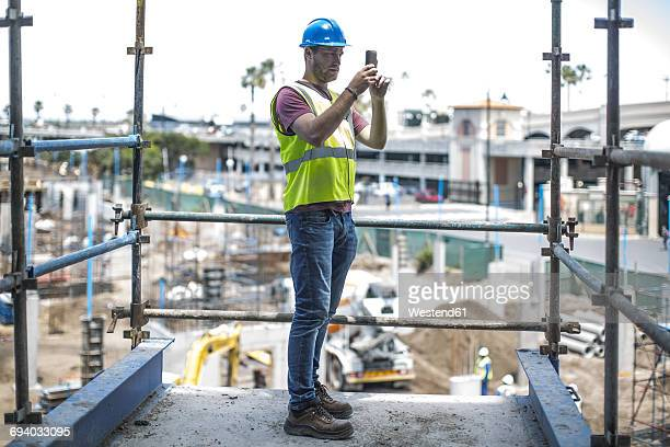 Construction worker on construction site taking pictures with smart phone