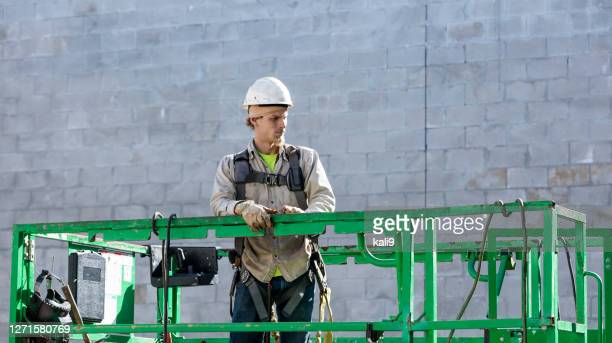 construction worker on scissor lift - safety harness stock pictures, royalty-free photos & images