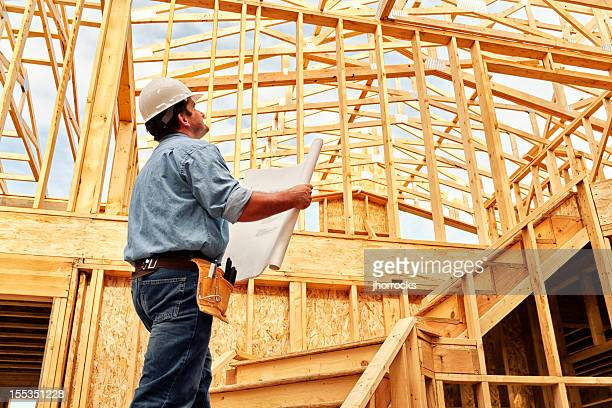 construction worker on site with plans - construction frame stock pictures, royalty-free photos & images