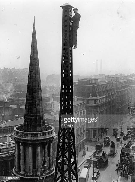 A construction worker on the BBC's radio tower Next to it the tower of All Soul's Church London England Photograph April 30th 1931