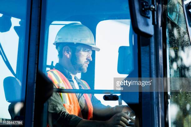 construction worker operating a backhoe - earth mover stock pictures, royalty-free photos & images