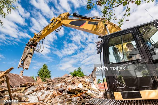 construction worker operating an excavator at a demolition site - demolishing stock pictures, royalty-free photos & images