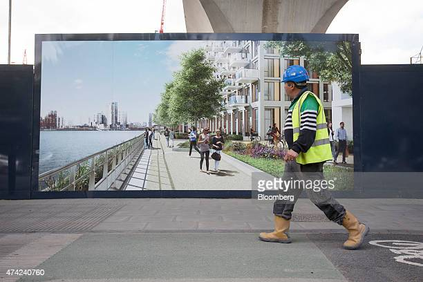 A construction worker passes an advertisement for the Royal Wharf residential and retail construction site developed by Ballymore Properties Ltd near...