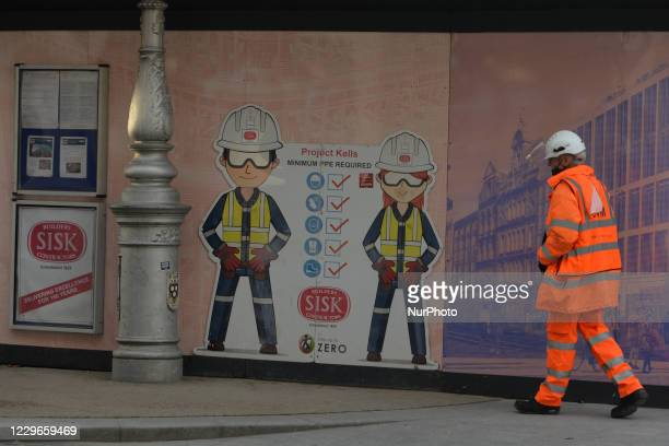 Construction worker passes by a PPE Rules sign in Dublin city center. On Tuesday, November 17 in Dublin, Ireland.