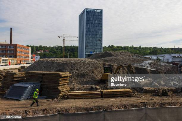 Construction worker passes concrete slabs and lumber on a residential apartment construction site, on a plot of brownfield land in the Vysoany...
