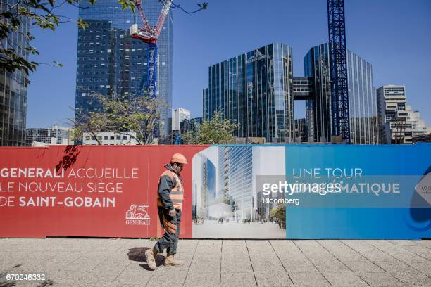 Construction worker passes hoardings beside the new headquarters of Cie. De Saint-Gobain SA, which are being built by Vinci SA, in the La Defense...